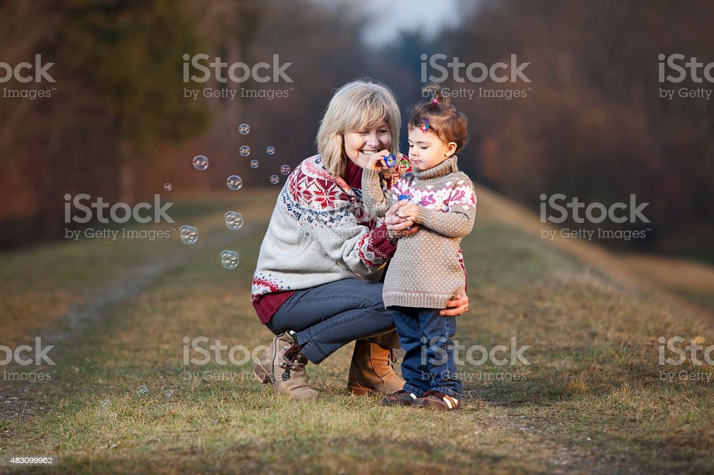 Grandmother and granddaughter blowing bubbles stock photo
