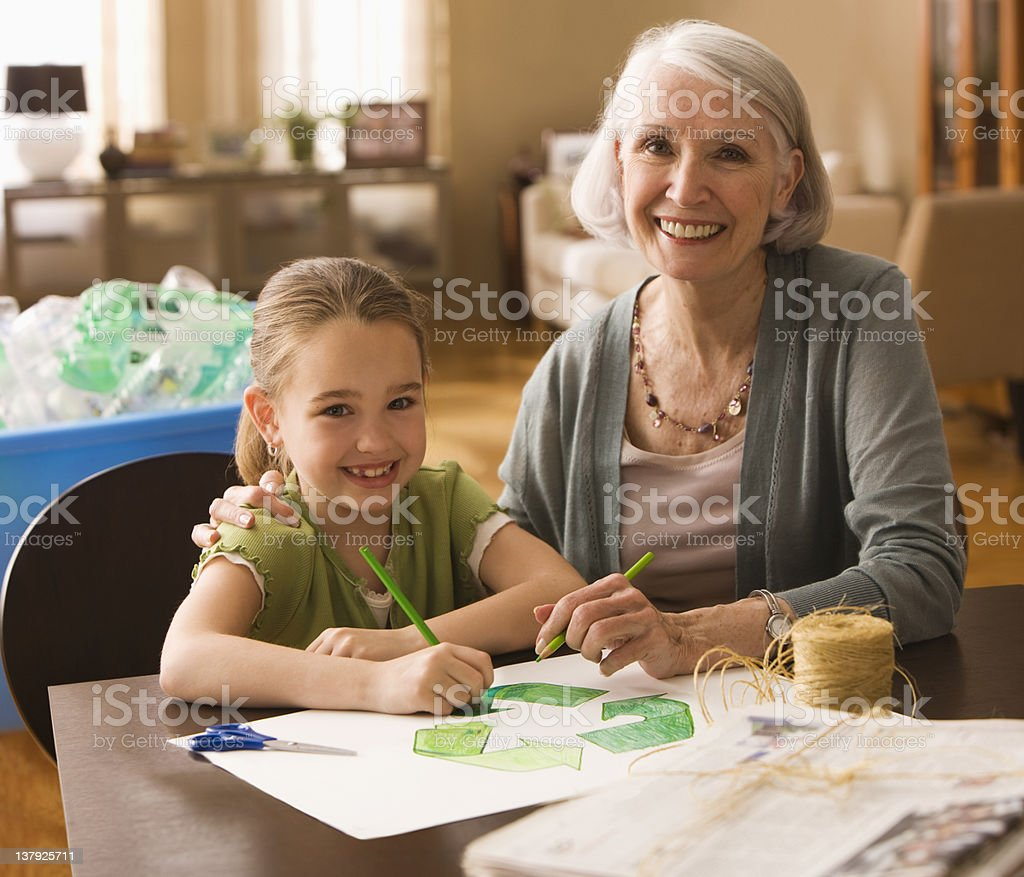 Grandmother and granddaughter coloring recycle sign royalty-free stock photo