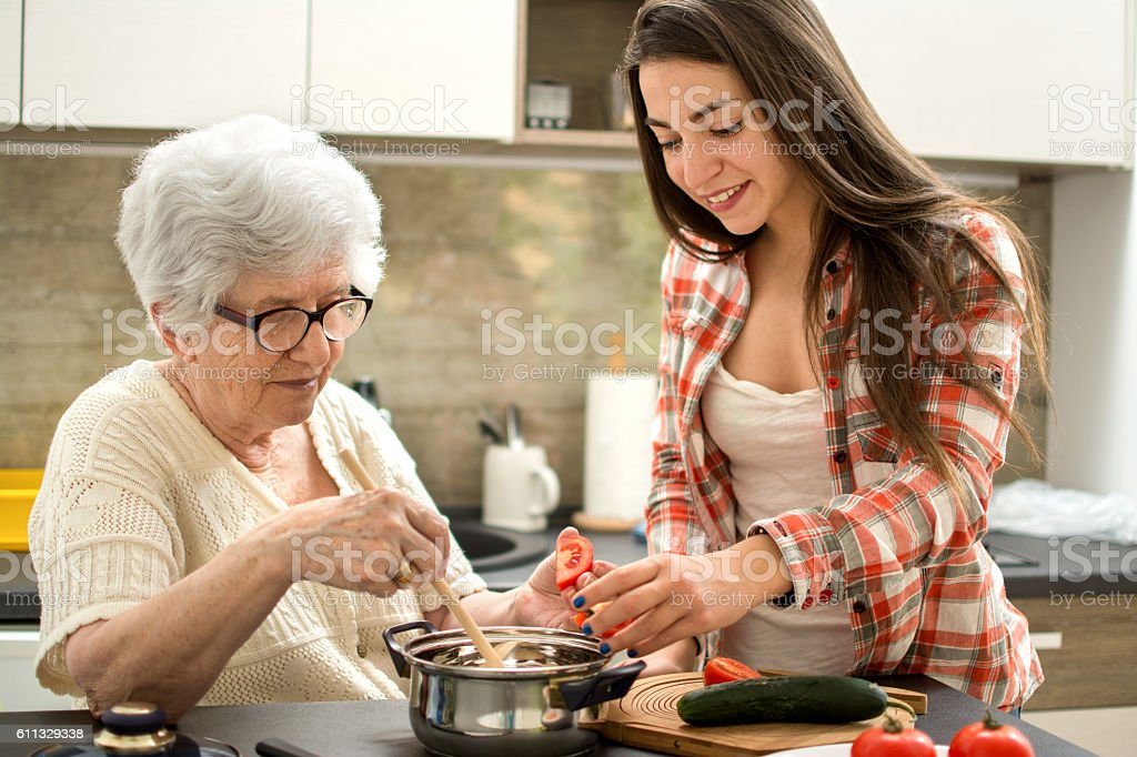 Grandmother and granddaughter cooking in the kitchen. stock photo