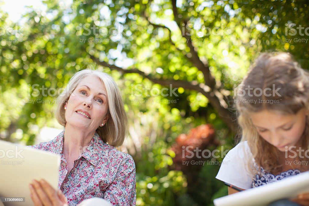 Grandmother and granddaughter drawing on sketch pads below trees royalty-free stock photo