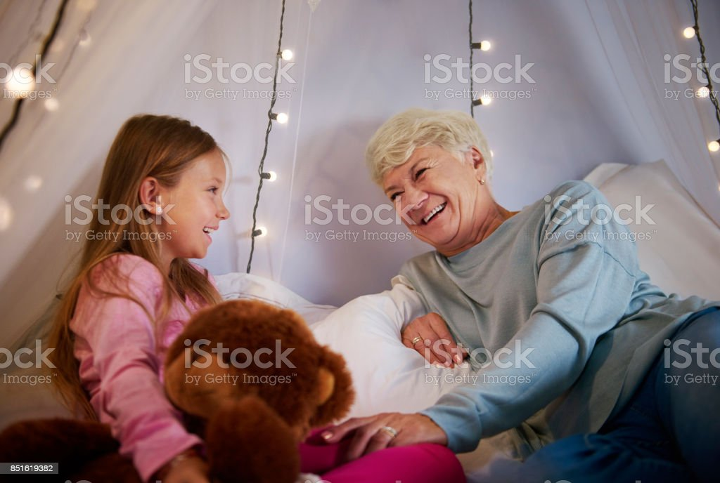 Grandmother and granddaughter enjoying in bedroom stock photo