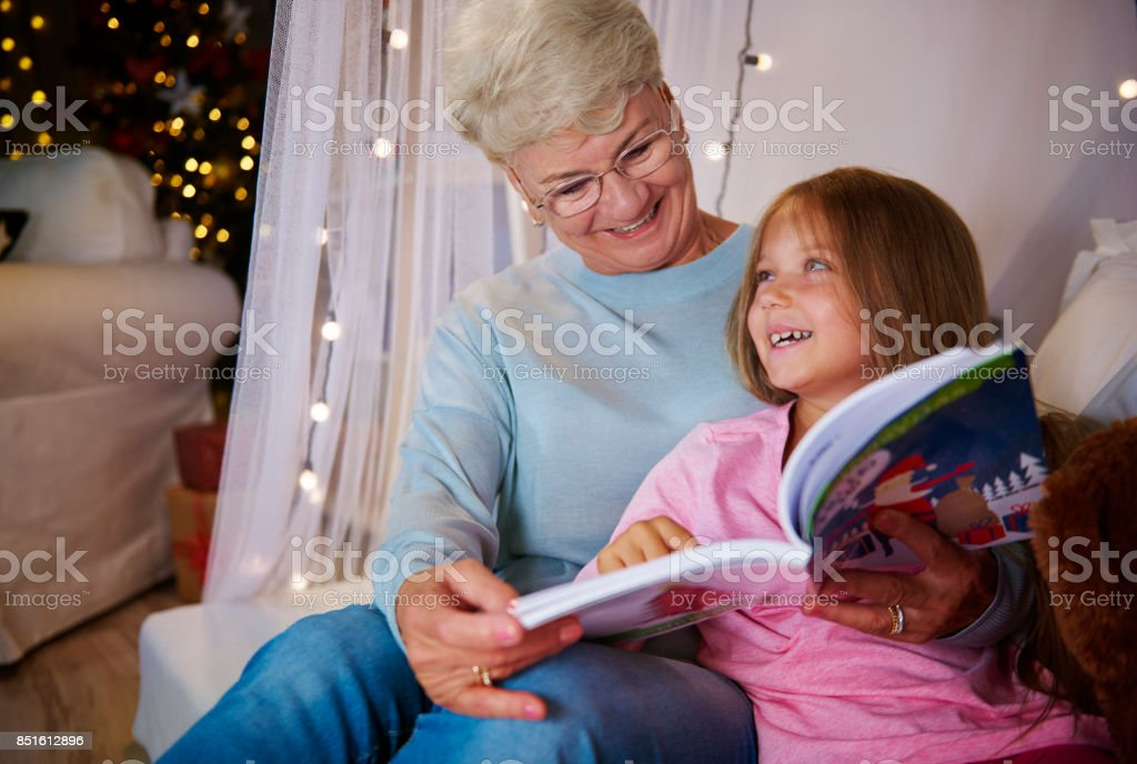 Grandmother and  granddaughter having a fun in bedroom stock photo