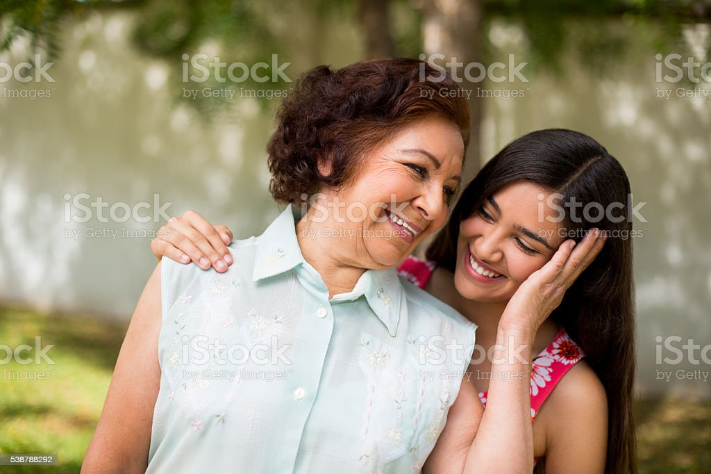 Grandmother and granddaughter holding each other dearly stock photo