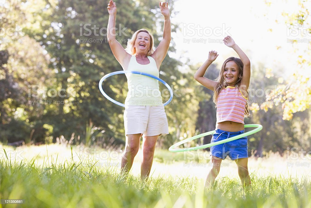 Grandmother and granddaughter hula hooping in park stock photo