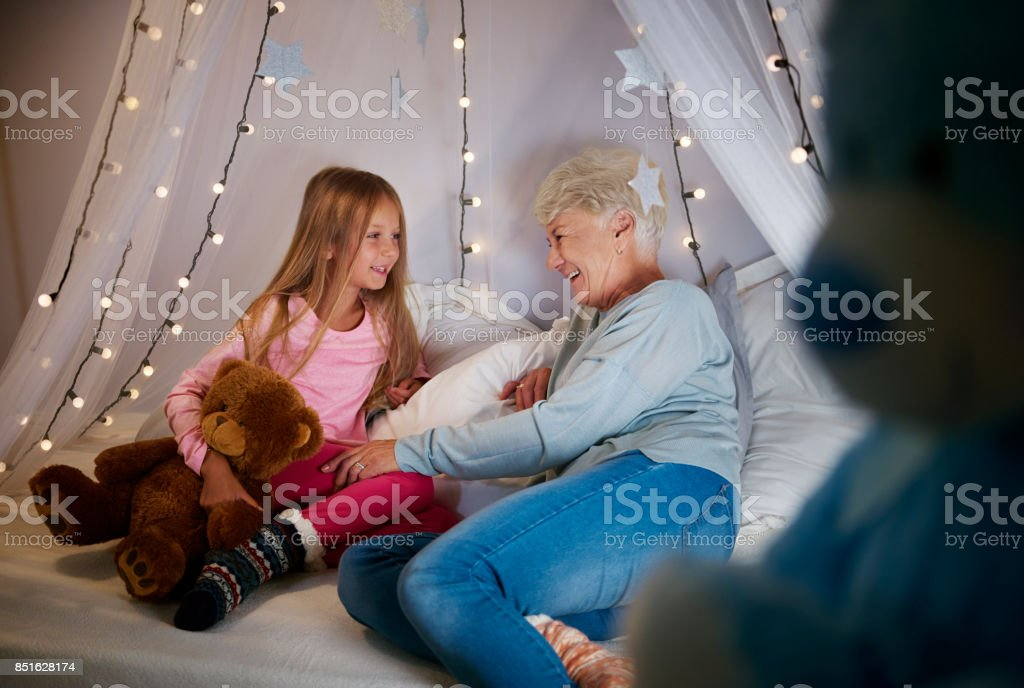Grandmother and granddaughter in bedroom stock photo