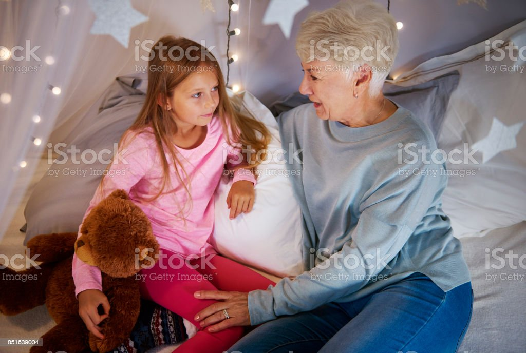 Grandmother and granddaughter interacting in bedroom stock photo