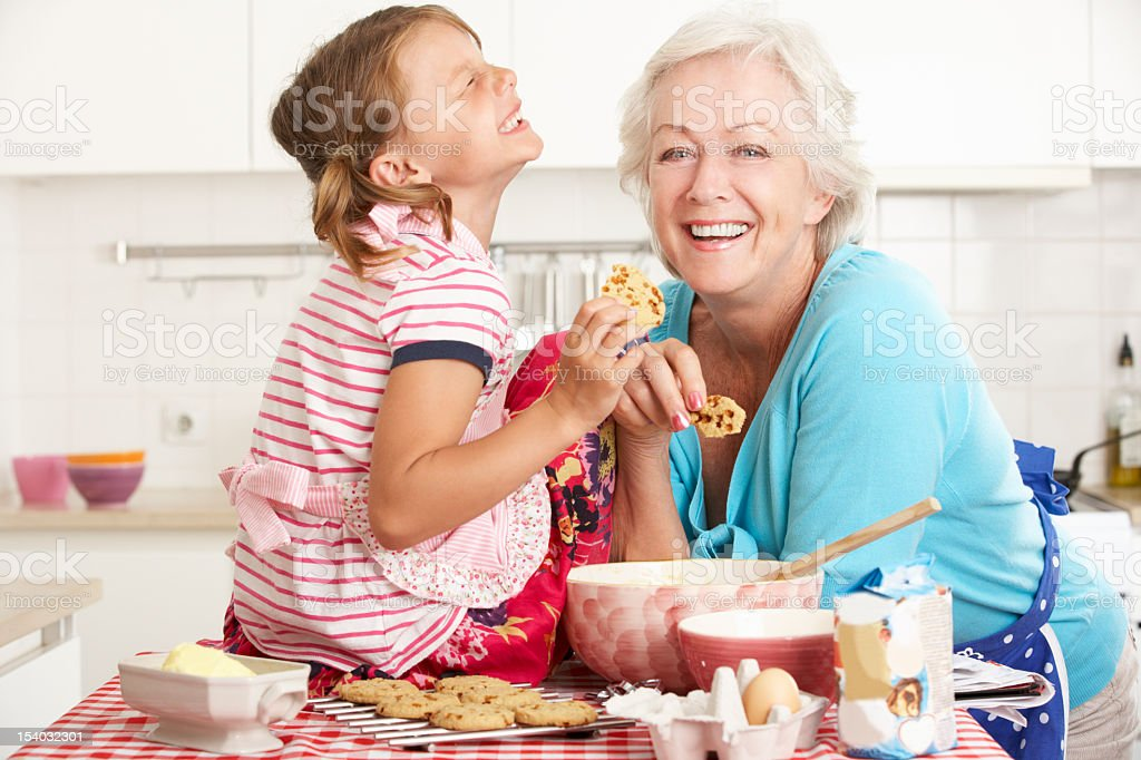 Grandmother and granddaughter laughing and baking in kitchen stock photo