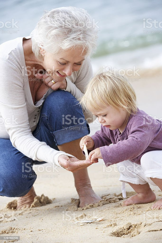 Grandmother And Granddaughter Looking at Shell On Beach stock photo