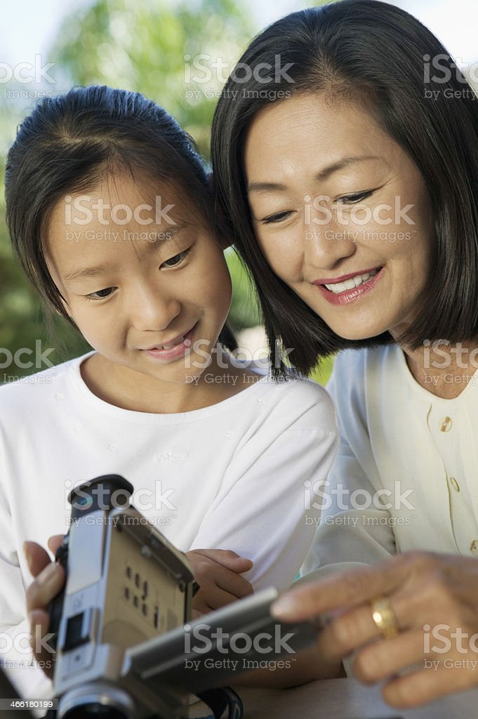 Grandmother And Granddaughter Looking At Video Camera royalty-free stock photo