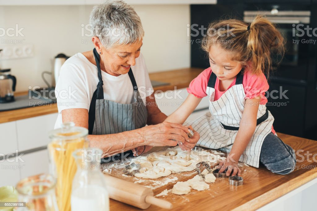 Grandmother and granddaughter making cookies stock photo