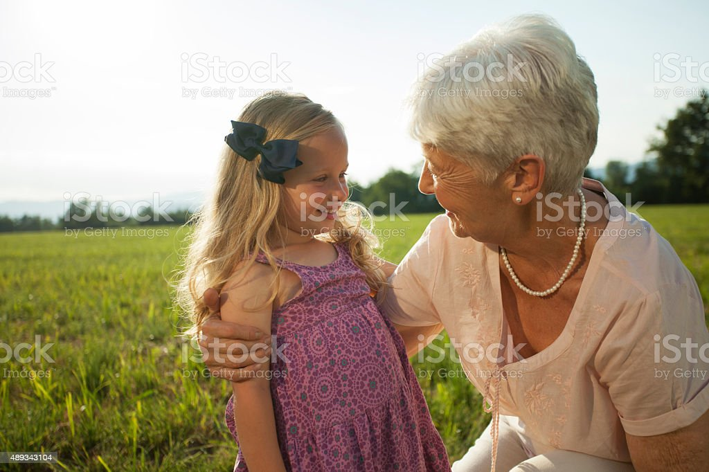Grandmother and granddaughter on meadow, smiling stock photo