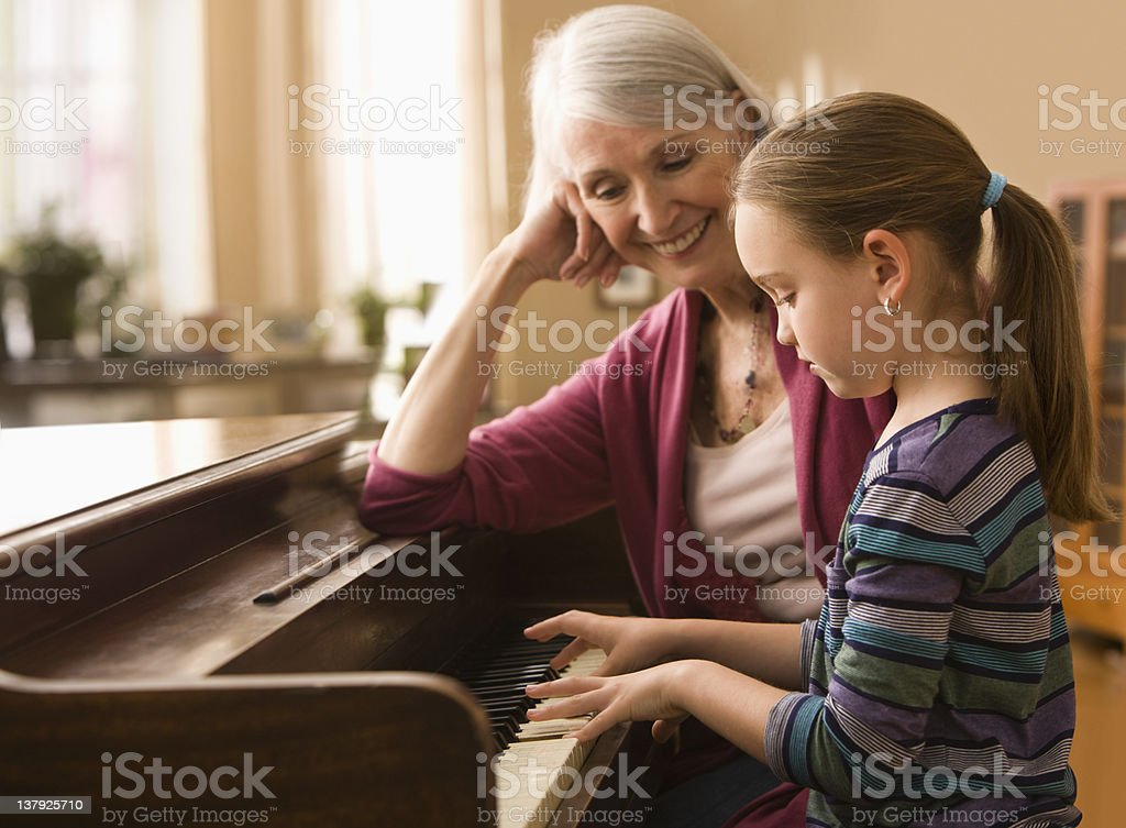 Grandmother and granddaughter  play piano stock photo