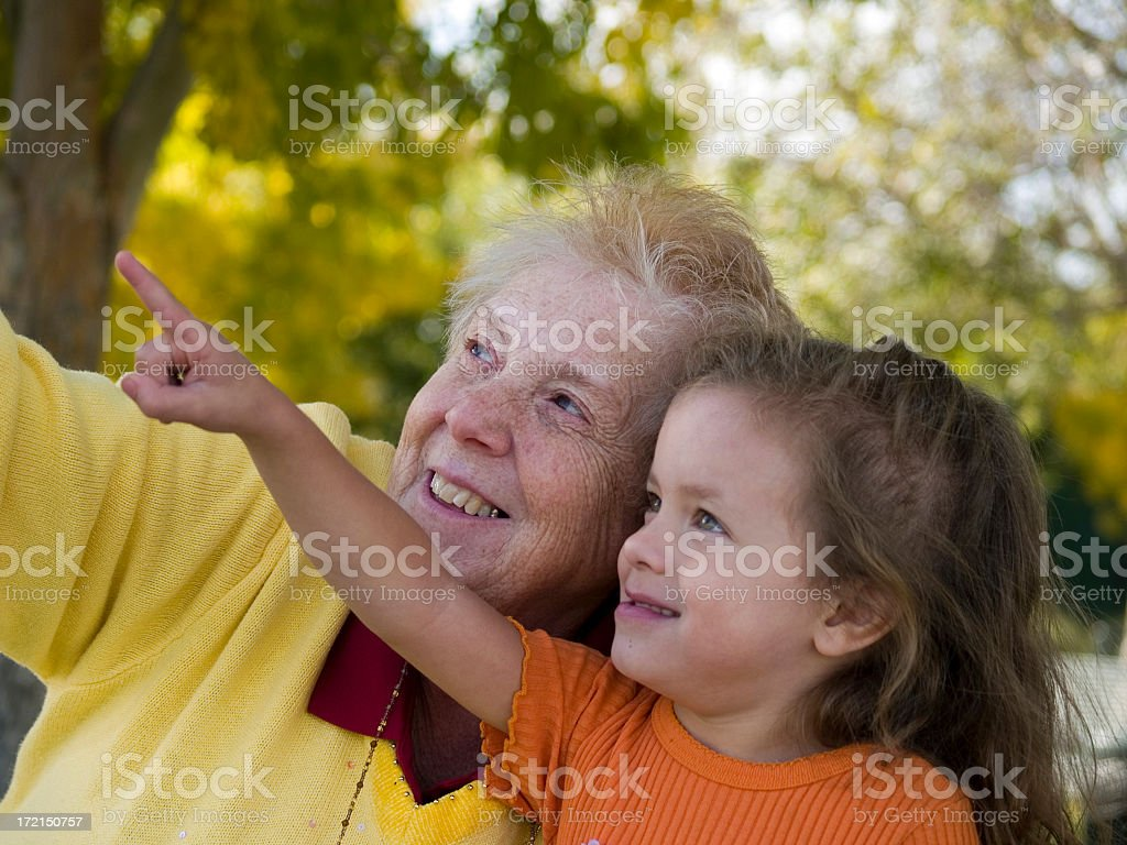 Grandmother and granddaughter point at something above them royalty-free stock photo