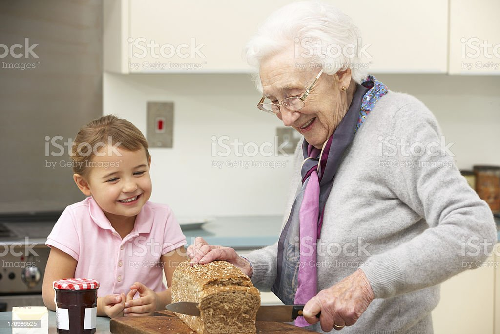 Grandmother and granddaughter preparing food in kitchen stock photo