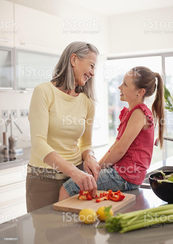 Grandmother and granddaughter preparing food together royalty-free stock photo