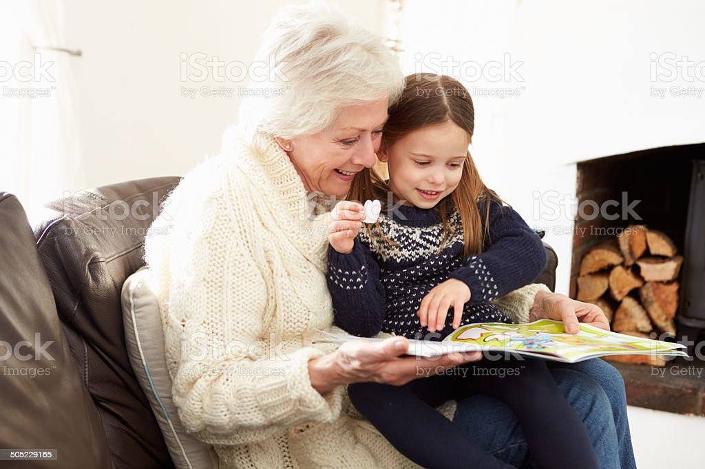 Grandmother And Granddaughter Reading Book At Home Together stock photo