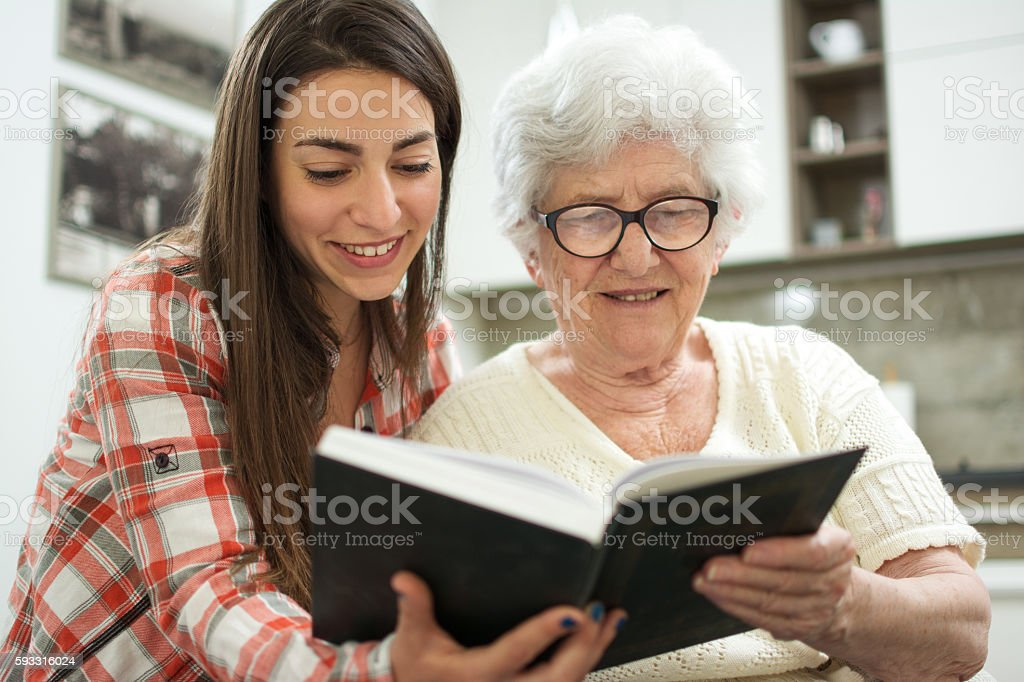 Grandmother and granddaughter reading book together at home. stock photo