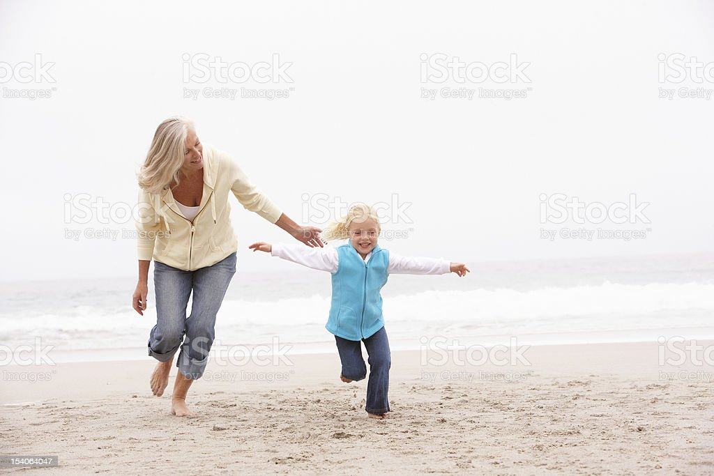 Grandmother And Granddaughter Running Along Winter Beach stock photo