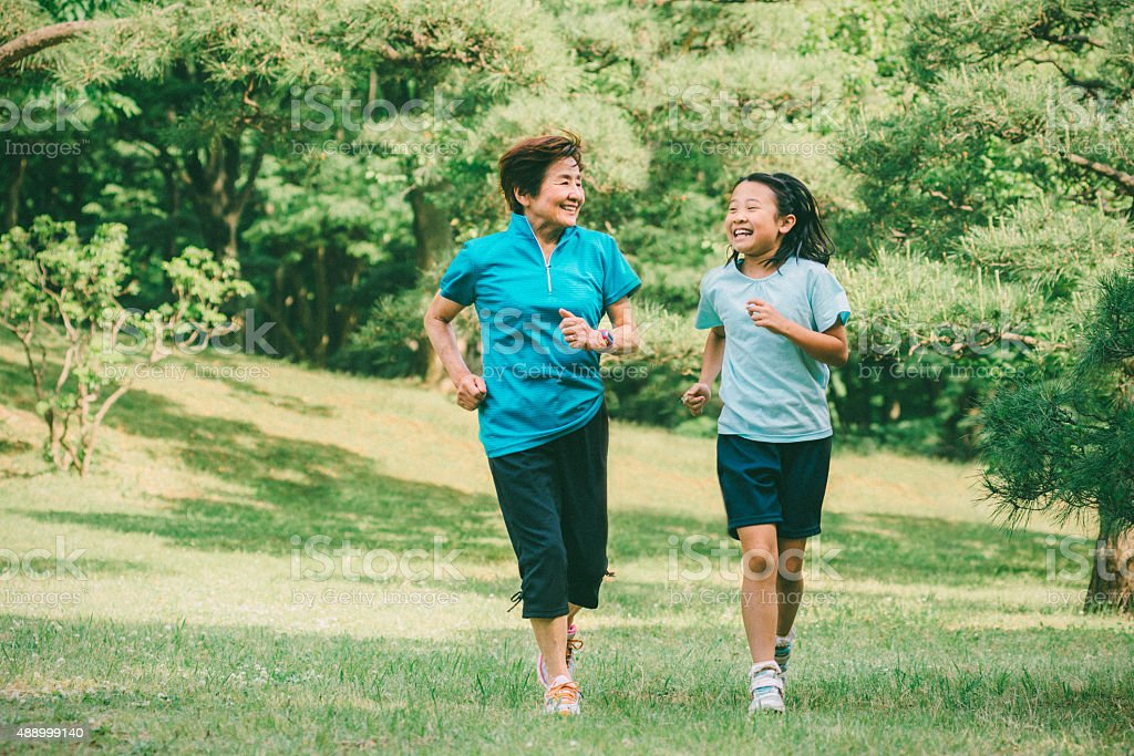 Grandmother and granddaughter running together stock photo