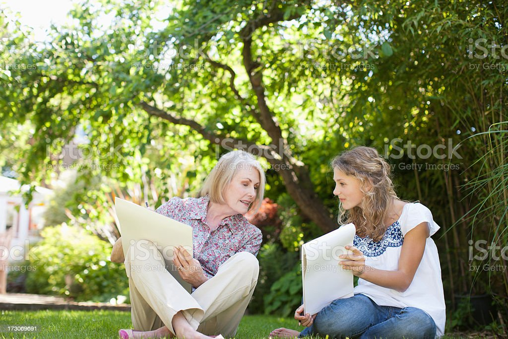 Grandmother and granddaughter sitting in grass and drawing on sketch pads royalty-free stock photo