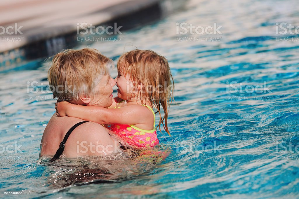 Grandmother and granddaughter swimming at pool stock photo