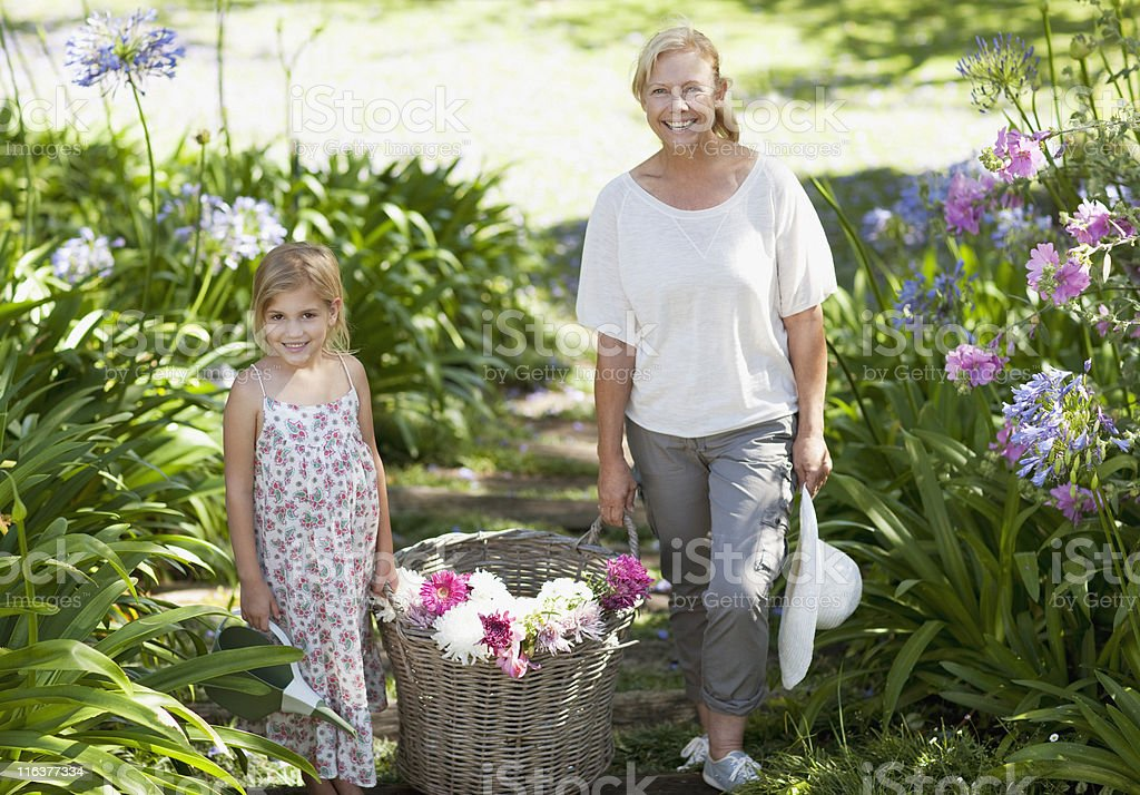 Grandmother and granddaughter with basket of flowers in garden royalty-free stock photo