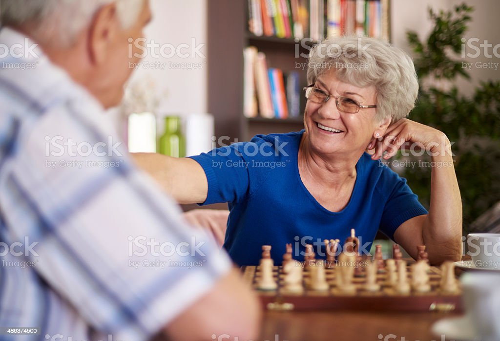 Grandmother and grandfather playing chess for relaxation stock photo
