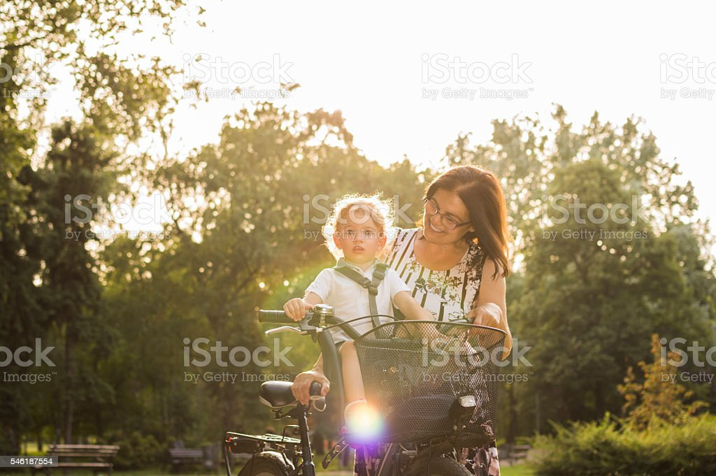Grandmother and grandson enjoy a bike ride stock photo