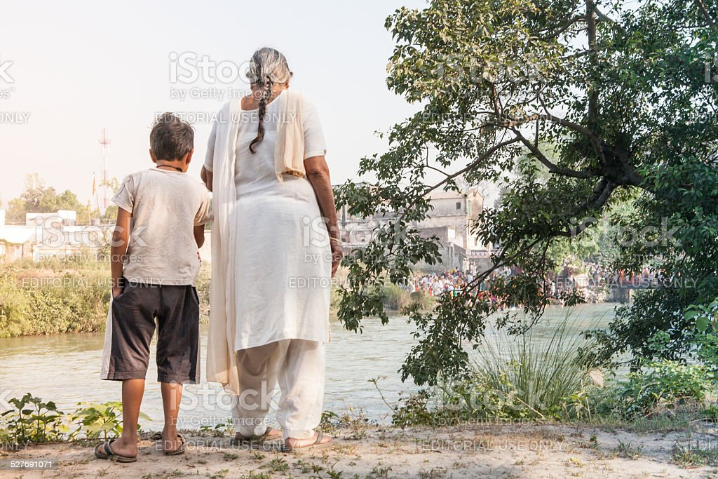 Grandmother and grandson looking at Ganges River stock photo