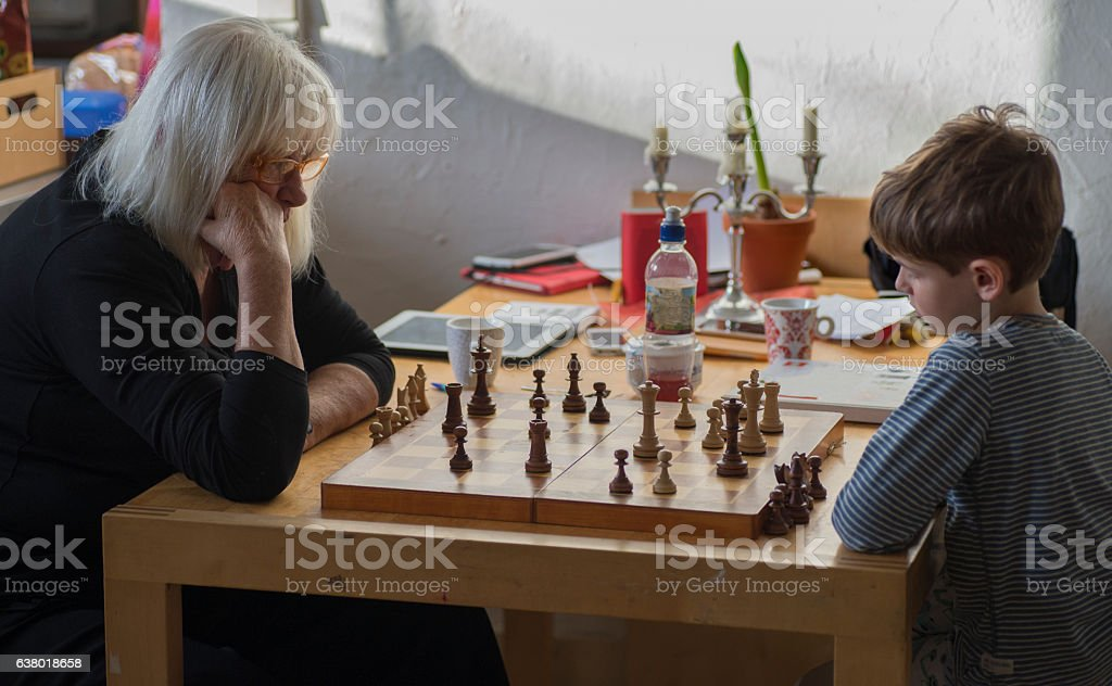 Grandmother and grandson playing chess at table stock photo