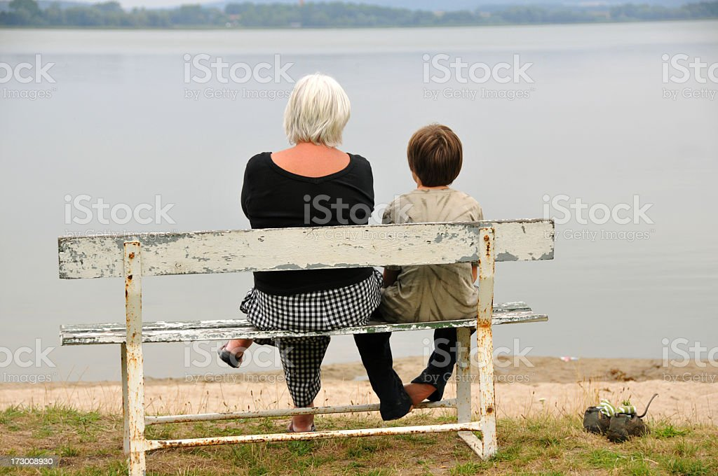 Grandmother and grandson sitting on a bench at the lake royalty-free stock photo