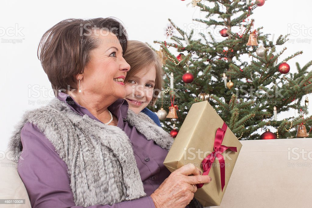 Grandmother and grandson smiling, Christmas tree in background stock photo
