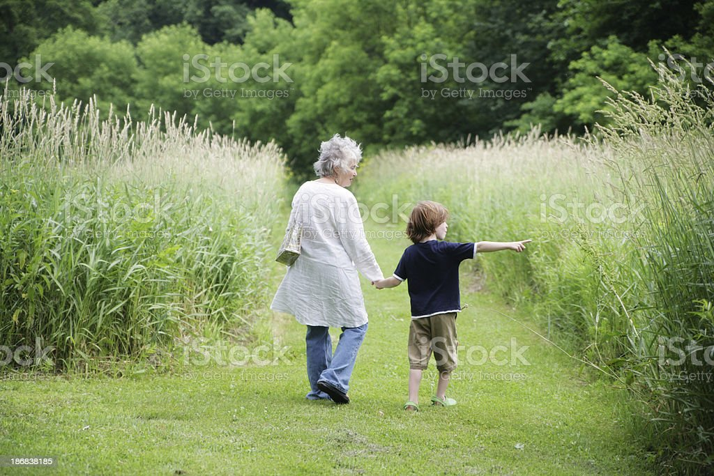 Grandmother and Grandson Taking a Walk on Beautiful Trail royalty-free stock photo