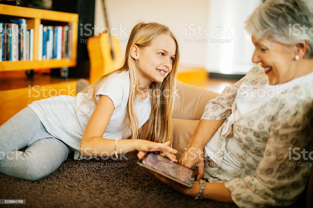 Grandmother and her granddaughter using a tablet at home stock photo