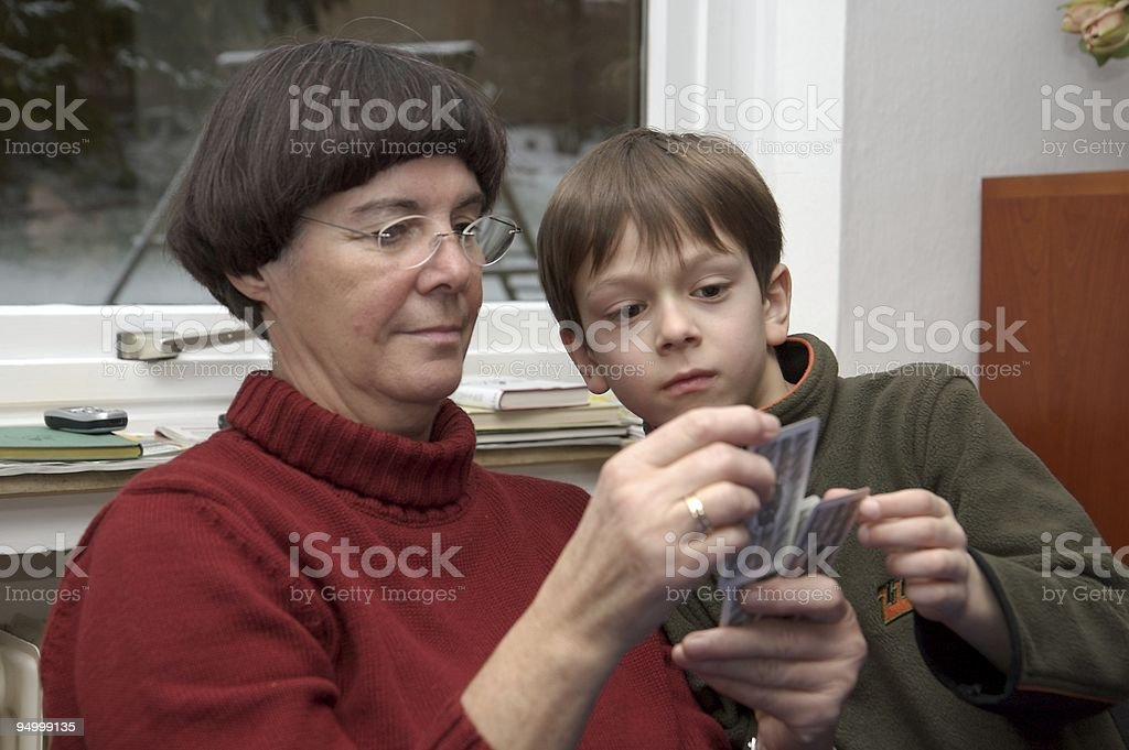 grandmother and little boy playing cards together royalty-free stock photo
