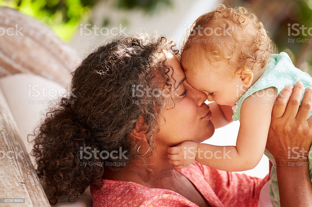 Grandmother At Home Playing With Granddaughter In Garden stock photo