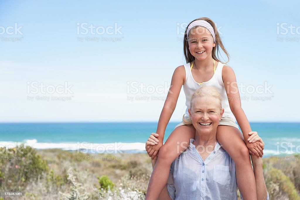 Grandmother carrying granddaughter on shoulders on beach royalty-free stock photo