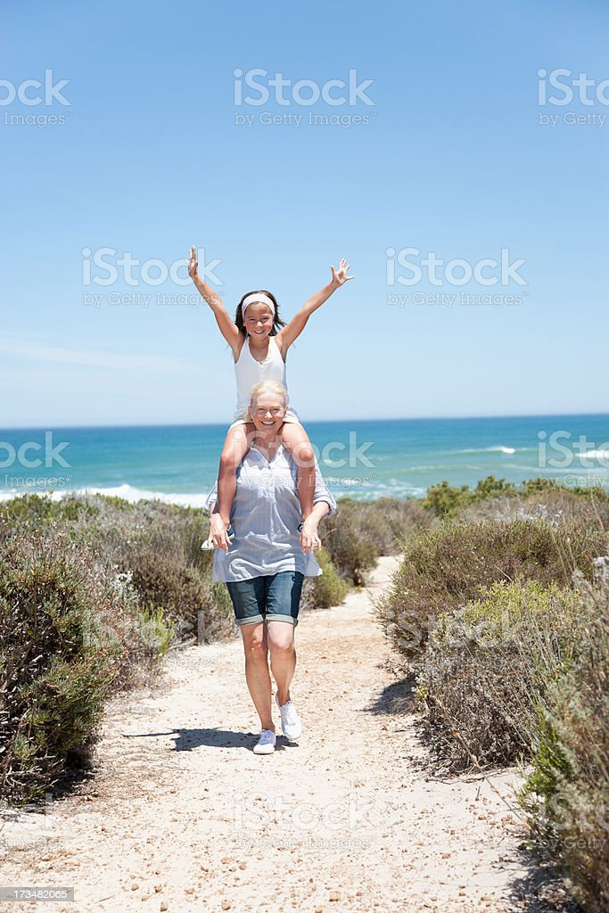 Grandmother carrying granddaughter on shoulders on beach stock photo