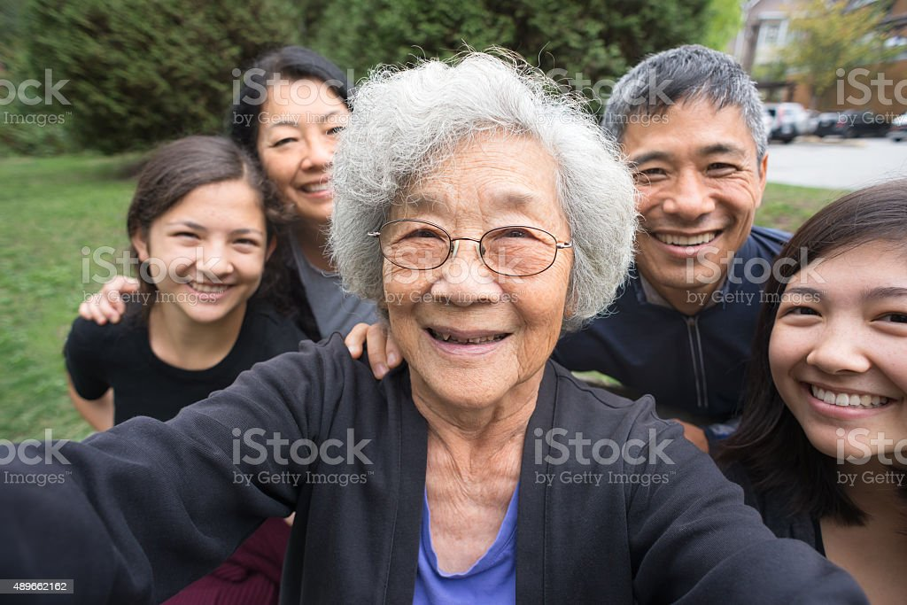 Grandmother, Children, Grandchildren Pose for Selfie, Care Home in Background stock photo