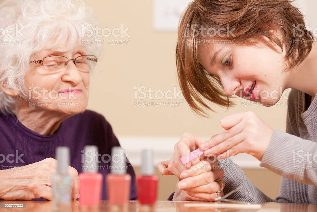Grandmother Enjoying Manicure From Granddaughter stock photo