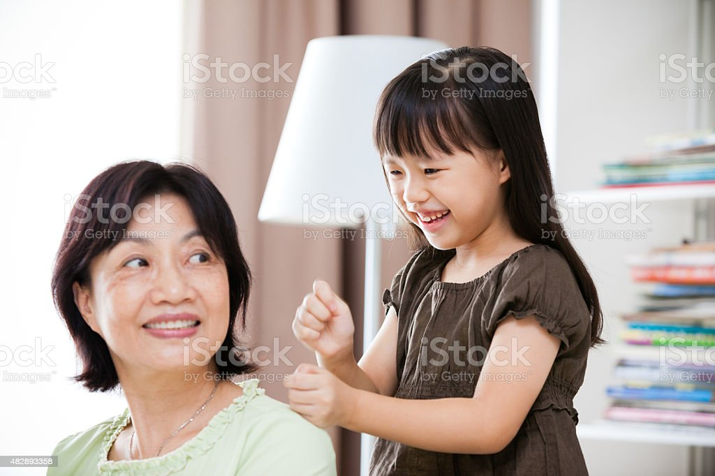 Grandmother Enjoying Massage from Granddaughter at Home stock photo