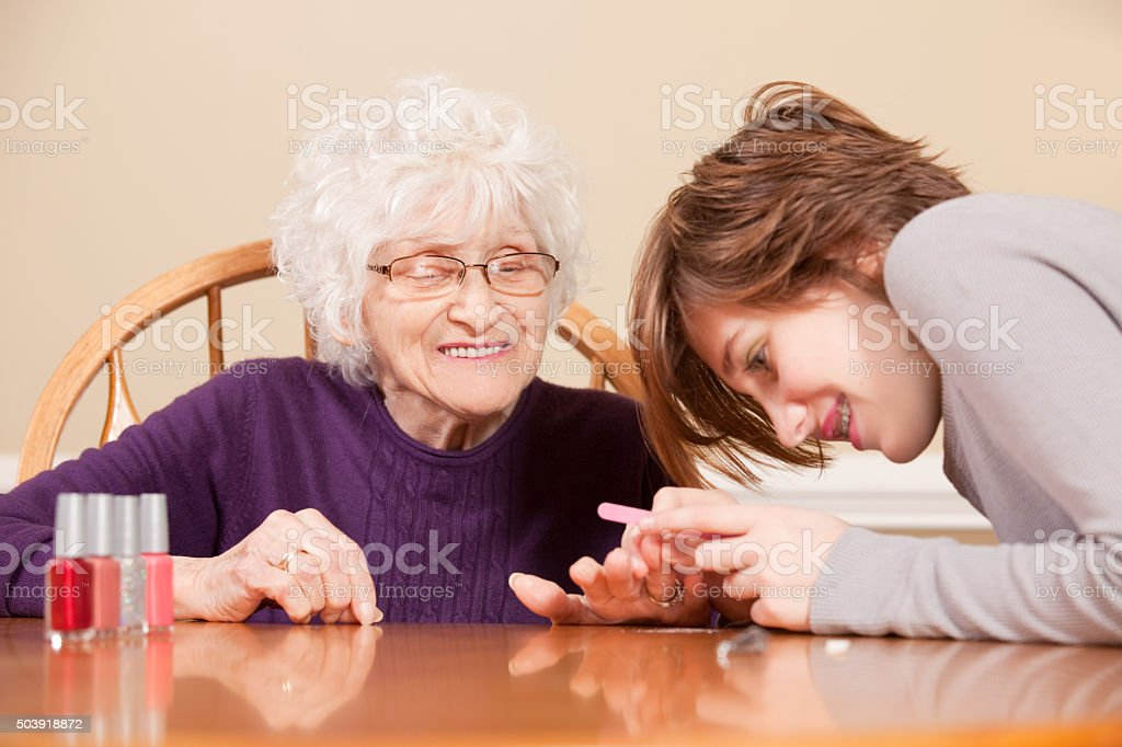Grandmother Getting Manicure From Granddaughter stock photo