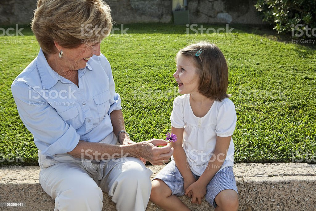 Grandmother giving flower to granddaughter stock photo