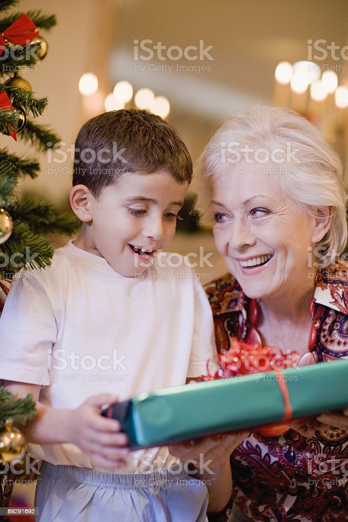 Grandmother giving grandson Christmas gift stock photo