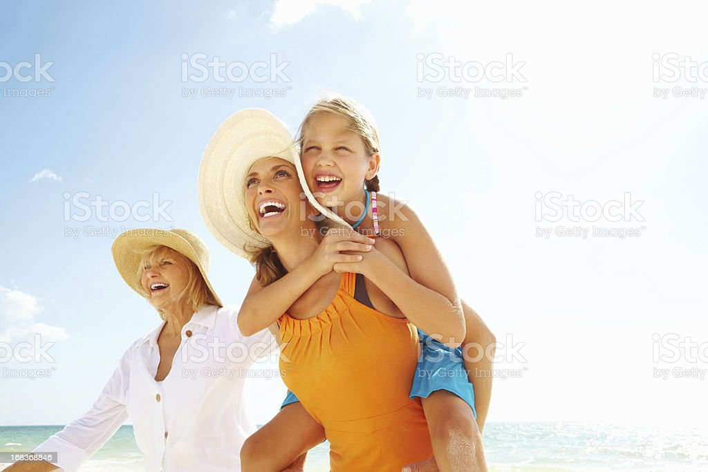 Grandmother, granddaughter and daughter enjoying on beach stock photo