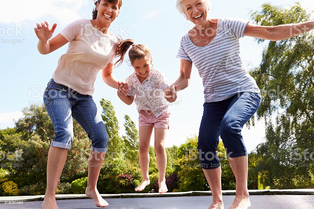 Grandmother, Granddaughter And Mother Bouncing On Trampoline stock photo