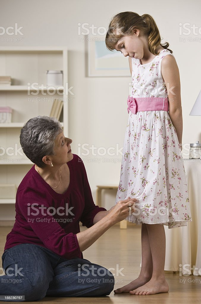 Grandmother Hemming Granddaughter's Dress stock photo