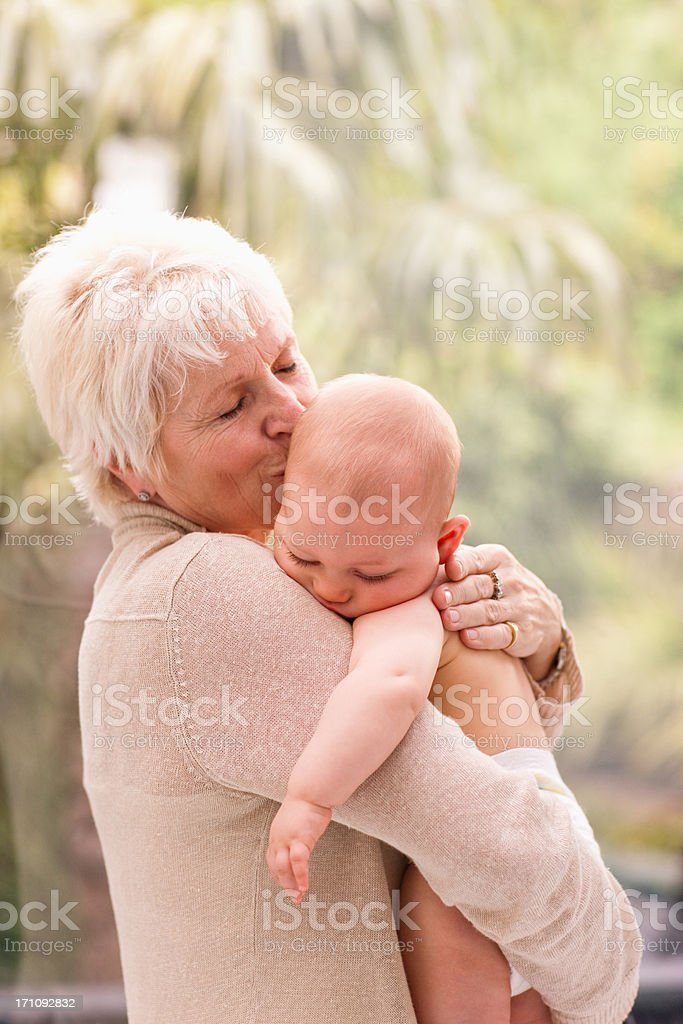 Grandmother holding and kissing baby royalty-free stock photo