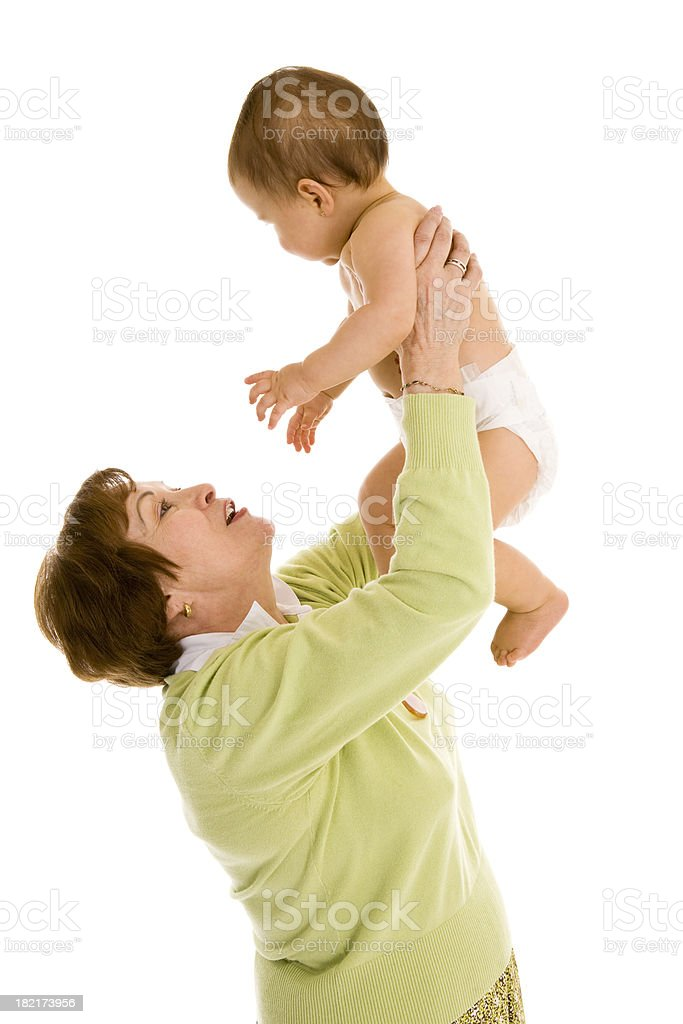 Grandmother holding baby overhead making a face royalty-free stock photo