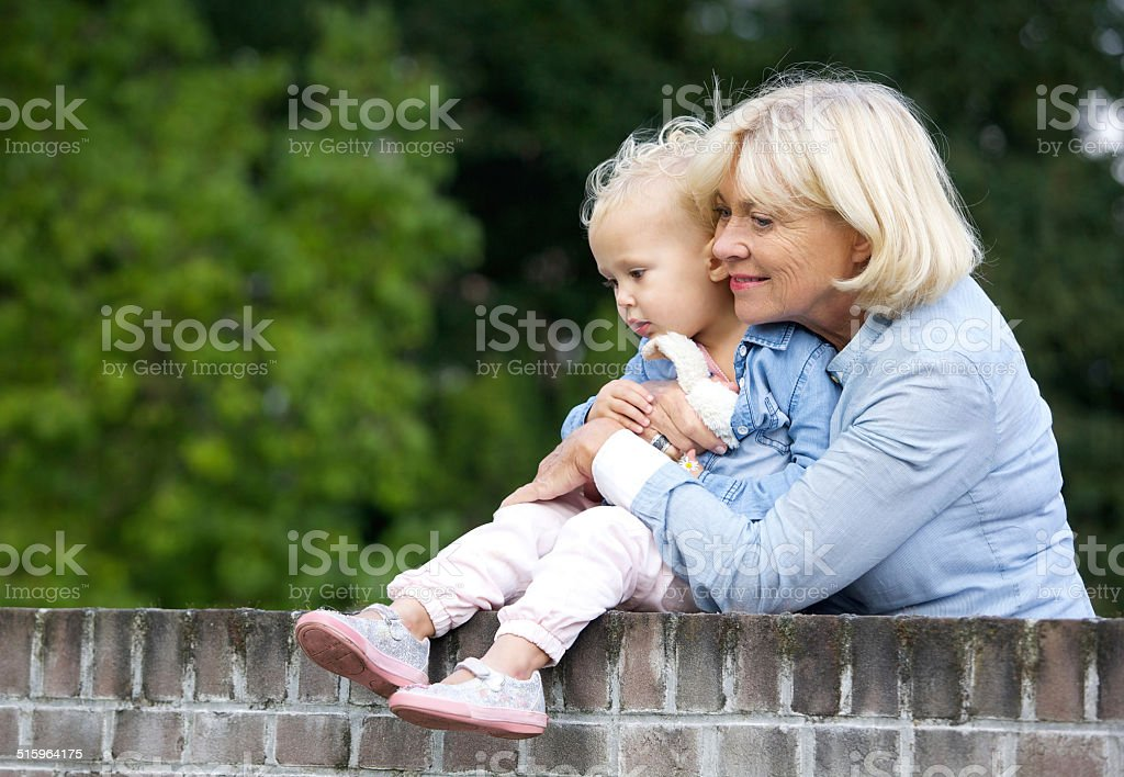 Grandmother holding cute baby girl stock photo